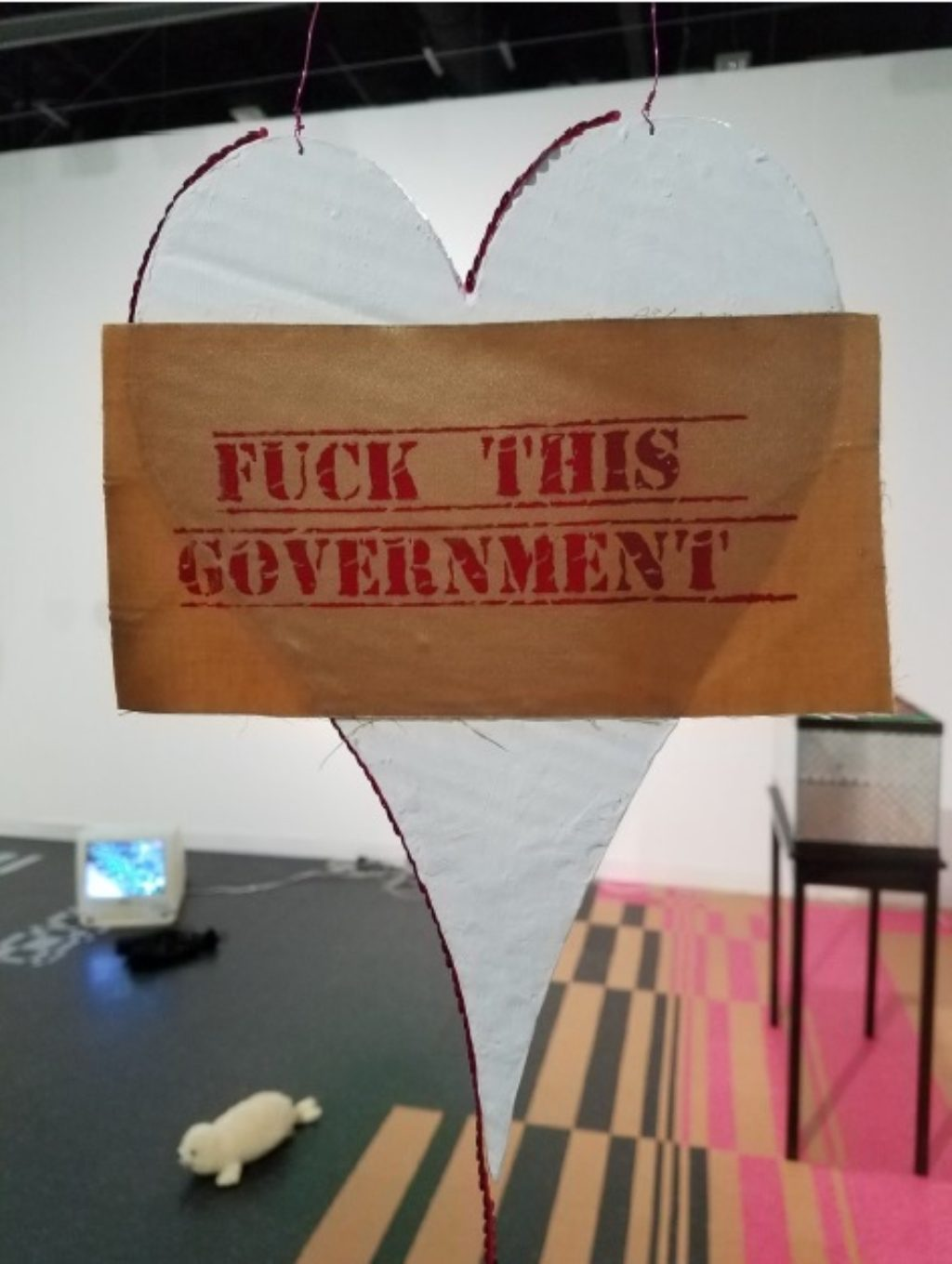 Maggie Lee, Fthis.gov, 2016 gesso, modge podge, cardboard, laser photocopy, acrylic, wire, silkscreen on fabric Heart: 13 x 9 inches (33.02 x 22.86 cm),Sequined string: 79 inches (200.66 cm),Hanging wire: 54 inches (137.16 cm) Photo courtesy of the gallery.