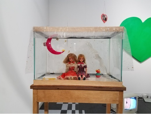 Maggie Lee, Maiden JP, 2016 Jenny dolls, glass tank, handmade paper, wire, vintage pet toys, hamster bedding, clear patterned plastic, stained maple table, 50 x 17 x 10 inches (127.00 x 43.18 x 25.40 cm)